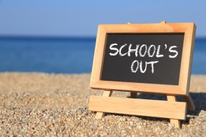 Blackboard with School's out text on the beach